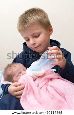 Six year old sibling feeding his newborn baby sister. - stock photo