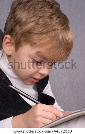 Six years boy sitting and writing in notebook