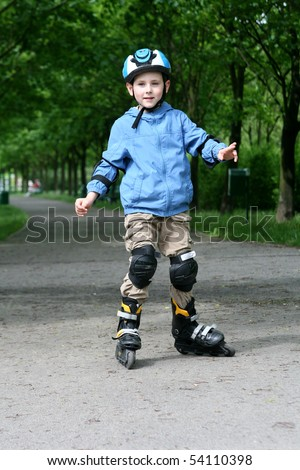 Six years old boy learning to ride on rollerblades. Boy with helmet and protectors. - stock photo