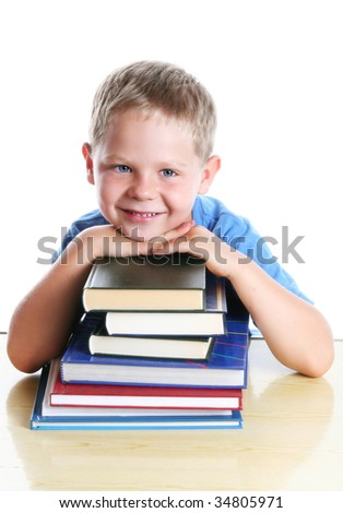 Six years old boy sitting at the table with a pile of books. Isolated on white. - stock photo