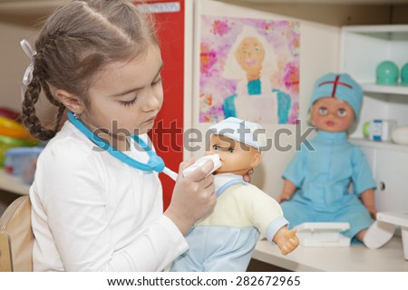 Six years old girl playing doctor with a doll in the nursery - stock photo