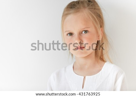 Six-years old girl with blond hair looking at you sideways with neutral emotions. Morning light and white clothes add simplicity and beauty to her attractive child appearance. - stock photo