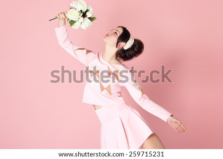 Sixties style fashion girl with bouquet of flowers over pink background. Romantic charming positive femininity concept. - stock photo