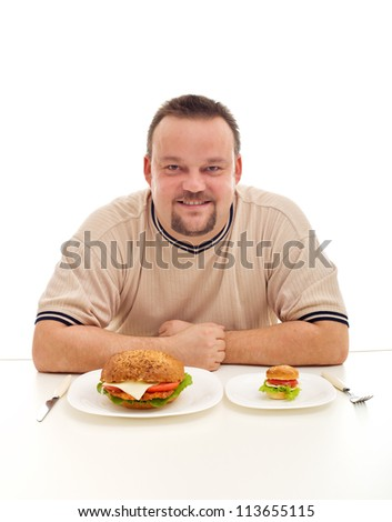 Size matters in your diet - overweight man pondering how much to eat - stock photo