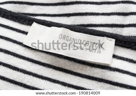 Size tag label on black and white striped knitted cloth - stock photo