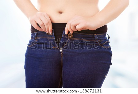 Size 40/42 woman zipping tight jeans, obesity and overweight concept - stock photo