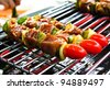 Sizzling barbecue sticks with meat and vegetables - stock photo
