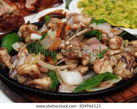 Sizzling bullfrog with vegetables served on iron plate - stock photo