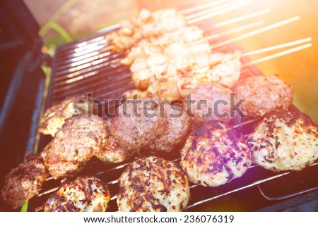 Sizzling burgers and chicken kebabs on hot barbecue outdoor in the evening sun. - stock photo