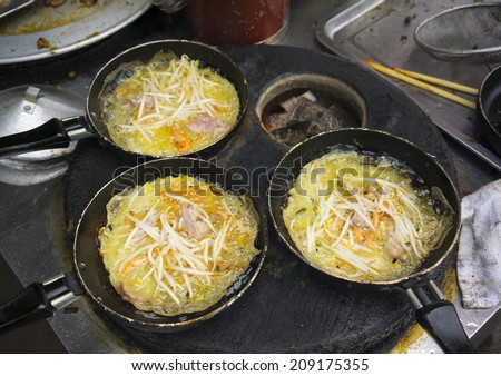 Sizzling cake, named for the loud sizzling sound it makes when the rice batter is poured into the hot skillet - stock photo
