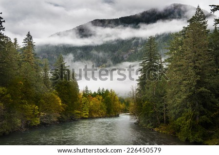 Skagit River. Low clouds and changing colors are a sure sign that fall is in full swing in the North Cascade mountains in this idyllic scene on the Skagit River in Washington state. - stock photo