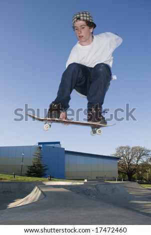 Skate boarder jumping over ramp - stock photo
