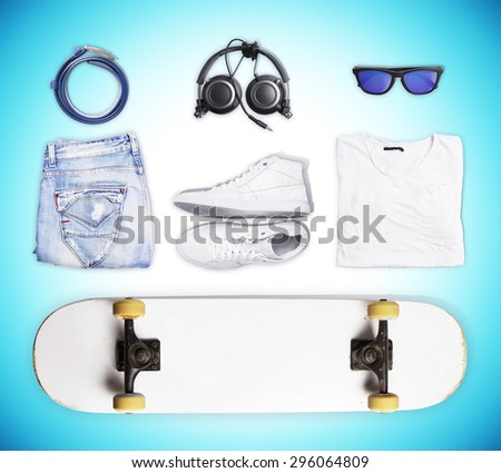 skateboard and wear and accessories on blue background - stock photo