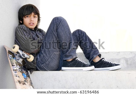 Skateboard kid: Boy sitting on concrete steps with his skateboard. He looks bored or not happy about something. White copy-space. - stock photo