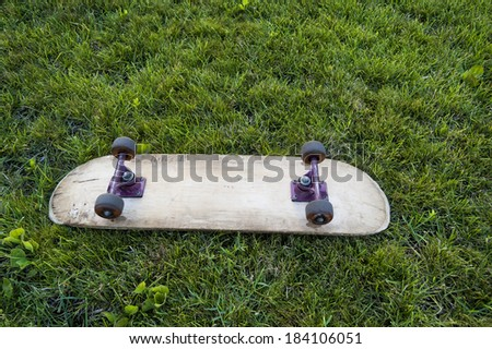 skateboard on the green grass - stock photo
