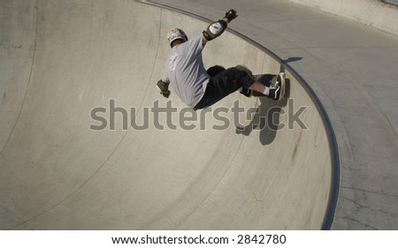 Skateboarder at McInnis County Park Skate Park in San Rafael, California rolls on a near vertical wall.