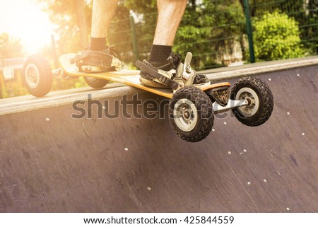 Skateboarder at skateboard park with mountainboard. Lens flare effect. - stock photo