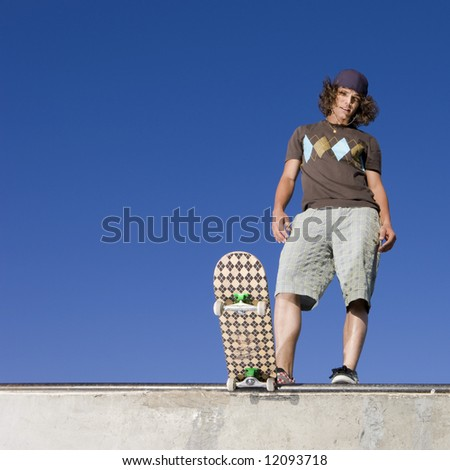 Skateboarder at top of half pipe - stock photo
