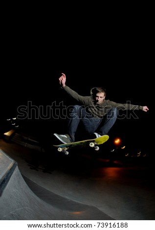 skateboarder blasting a big ollie at night at the local skatepark. - stock photo