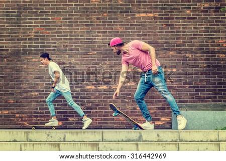 Skateboarder  boys by  brick wall - stock photo