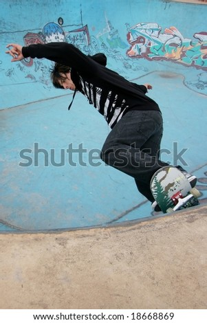 Skateboarder coming up to the railing in bowl - stock photo