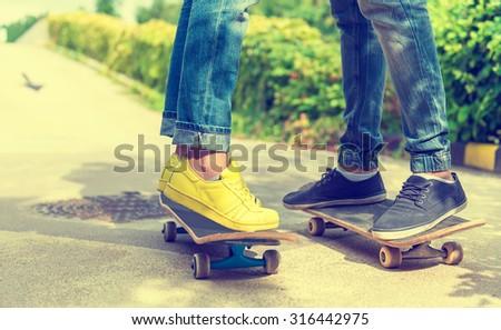 Skateboarder detail photo, women's and men's feet - stock photo