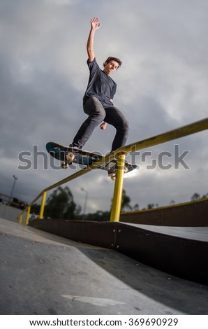 Skateboarder doing a board slide over the rail at the skate park. - stock photo