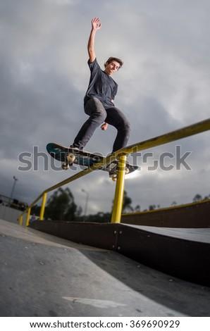 Skateboarder doing a board slide over the rail at the skate park. - stock photo