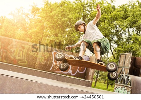 Skateboarder doing a jumping trick at skateboard park with mountain board. Lens flare effect. - stock photo