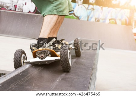 Skateboarder doing a jumping trick at skateboard park with mountainboard. Lens flare effect. - stock photo