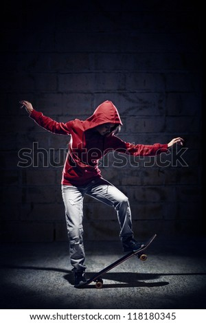 Skateboarder doing trick with grunge background red hoodie and skill - stock photo