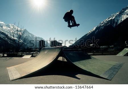 skateboarder in a skatepark with the French alps in the background