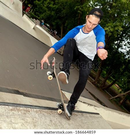 Skateboarder jumping in halfpipe at the skatepark - stock photo