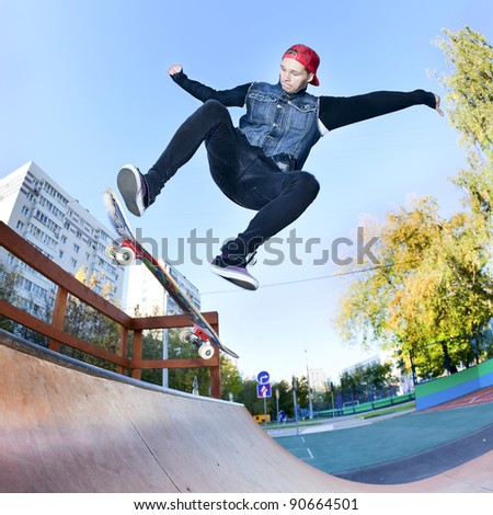 Skateboarder jumping in the halfpipe - stock photo