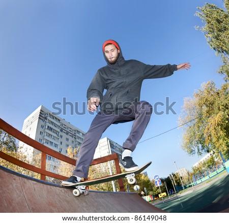 Skateboarder jumping in the halfpipe. Shooting fisheye lens optics - stock photo