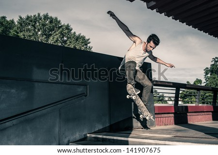 Skateboarder jumping stairs in the street. - stock photo