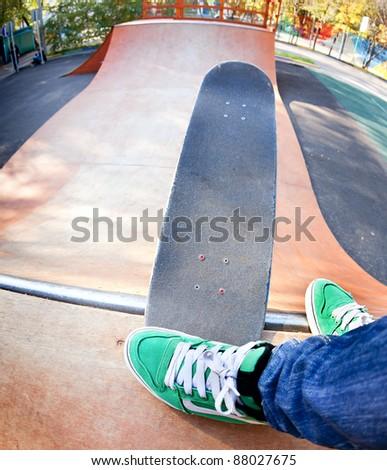Skateboarder legs before jumping in the halfpipe.  Shooting fisheye lens optics - stock photo