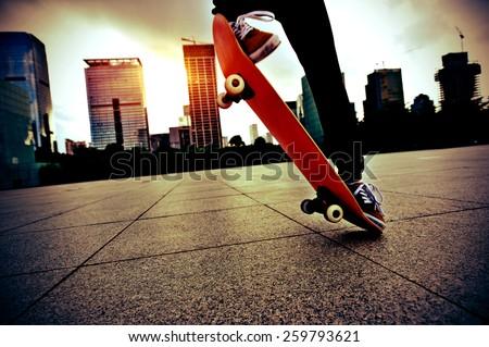 skateboarder legs skateboarding trick ollie  at city skate park - stock photo