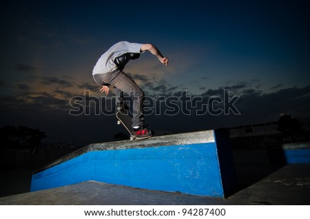 Skateboarder on a grind at the local skate park. - stock photo