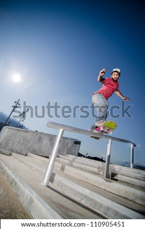 Skateboarder on a slide at the local skate park. - stock photo