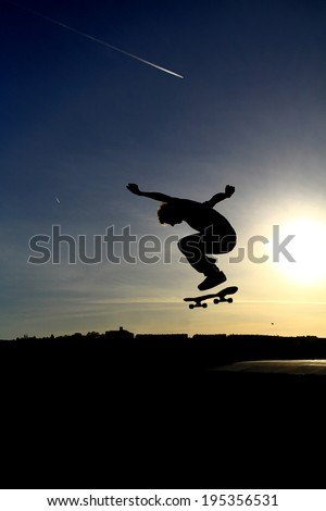 Skateboarder performing an aerial skateboarding jump trick - stock photo