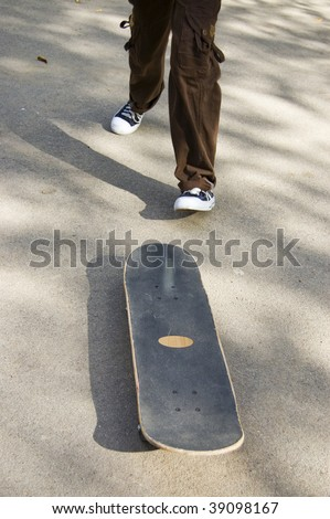 Skateboarder running to his skate in order to make a trick - stock photo