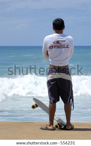Skateboarder watches surfers. - stock photo