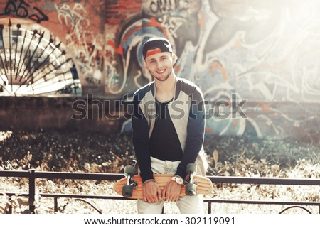 Skateboarder with black cap and sunglasses in front of graffiti wall. - stock photo
