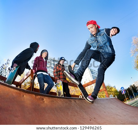 Skateboarder with friends in skatepark jumping in the halfpipe - stock photo