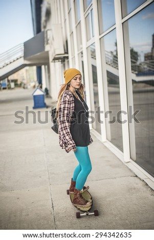 skateboarding woman in the city against glass building in perspective Beautiful young adult girl with long board Female wear yellow hat and blue modern tights Reflection in glass window  - stock photo