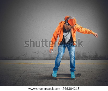 Skater boy runs and listens to music - stock photo