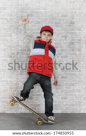 Skater boy showing V-sign in front of brick wall.