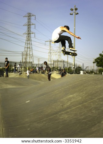 Skater getting air with other skaters in the background. Focus is on skater going big. - stock photo