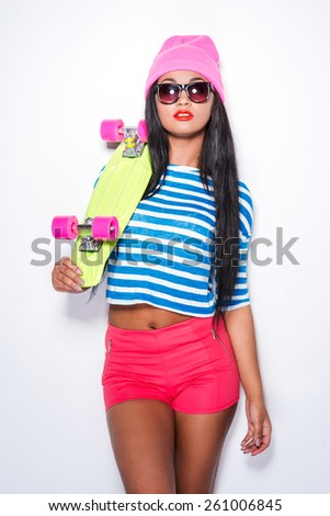 Skater girl. Attractive young African woman in funky clothes carrying colorful skateboard and looking at camera while standing against white background - stock photo